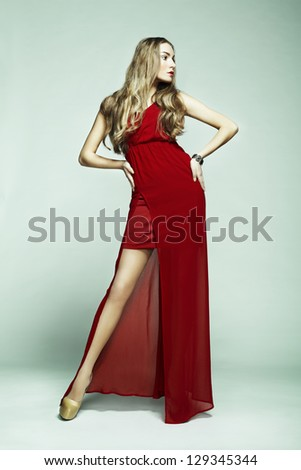 Fashion photo of young magnificent woman in red dress. Studio photo