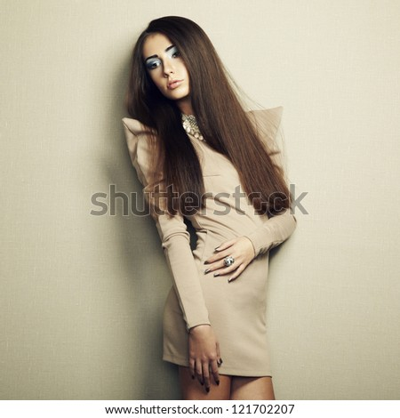 Fashion photo of young sensual woman in beige dress. Fashion photo