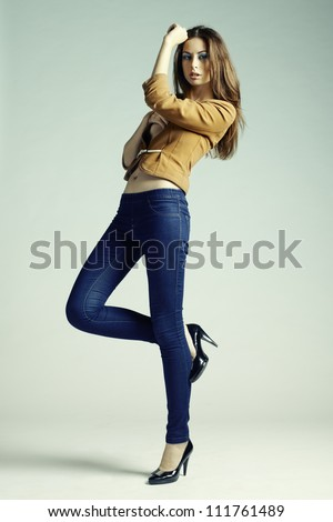 Fashion photo of young sensual woman in jeans. Studio photo