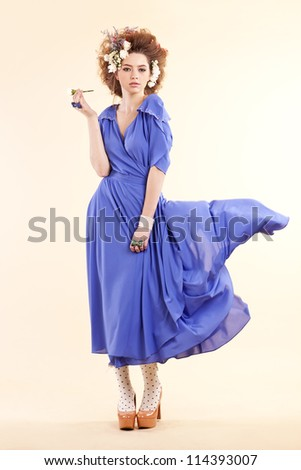 Fashion photo of young sensual woman in purple dress on yellow background