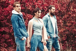 Fashion photo of young stylish company in trendy jeans clothes over autumn trees with rad leaves.