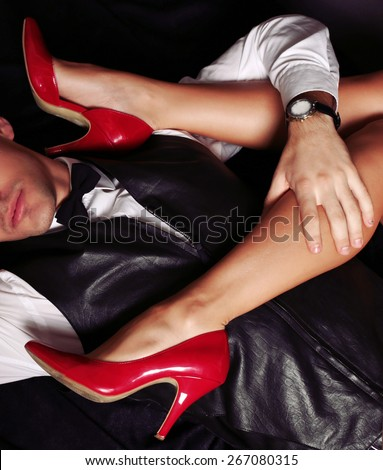 Fashion photo with sexy couple of woman with long tanned legs in red heeled shoes and man wearing a formal suit and watch posing at studio