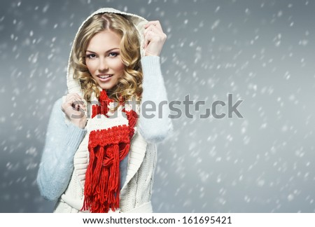 fashion picture of beautiful smiling blonde woman wearing a woolen sweater and knitted scarf