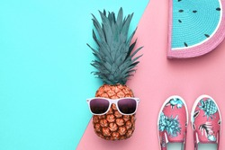 Fashion. Pineapple in sunglasses, beach outfit. Minimal pink flat lay, summer accessories, tropical pineapple. Creative art fashionable vacation concept, summertime party mood