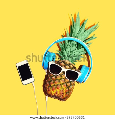 Fashion pineapple with sunglasses and headphones listens to music on smartphone over yellow background