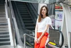 Fashion portrait - Beautiful asian young woman in white shirt and red sport pant posing infront of escalator.