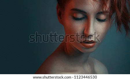 Fashion portrait in color lighting of beautiful red-haired girl face closeup, on dark blue background