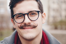 fashion portrait of a attractive hipster man outside. handsome guy with a vintage mustache, eyeglasses and a wristwatch.