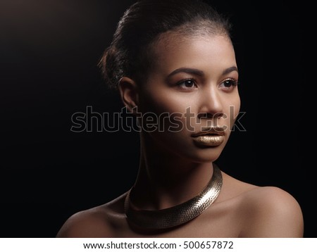 Fashion portrait of a beautiful naked african american woman with perfect smooth glowing mulatto skin, make up, full golden lips, shaved haircut and gold necklace, studio shoot #500657872