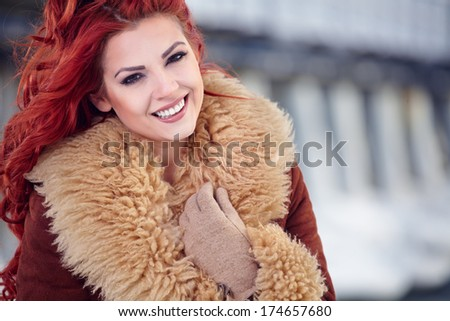 fashion portrait of a beautiful smiling girl with red hair in the winter