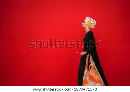 Fashion portrait of a beautiful, tall and fashionable woman of Middle Eastern descent. She is posing against a red, plain background.  #1090491578