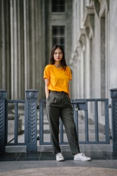 Fashion portrait of a beautiful, young and elegant Chinese Asian girl in smart casual clothing. She is wearing a yellow tee, olive green trousers and white sneakers against grey pillars during the day