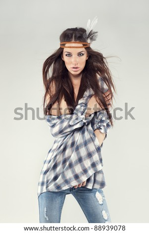 Fashion portrait of a beautiful young brunette dressed in hippie style. She is wearing a plaid shirt, skinny jeans and bandu. Wind is blowing through her hair. Taken in studio, gray background.