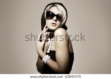 Fashion portrait of a beautiful young sexy woman wearing sunglasses