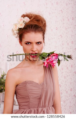 Fashion portrait of a blond girl with a rose in a mouth