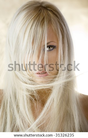 fashion portrait of a cute blond girl with long hair on yellow background