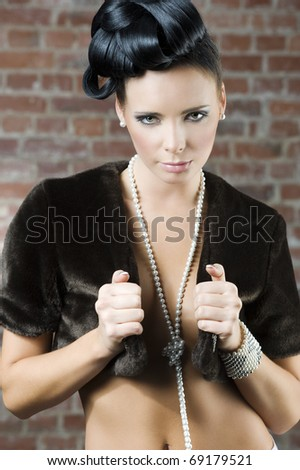 fashion portrait of a cute brunette wearing a brown fur and jewellery near a brick wall