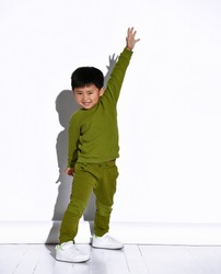 Fashion portrait of a cute little boy in a stylish green tracksuit against a white studio wall background. The boy raises his hands up - hurray, win