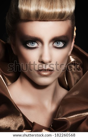 Fashion portrait of a girl in gold color
