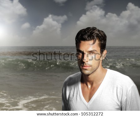Fashion portrait of a handsome man against ocean background