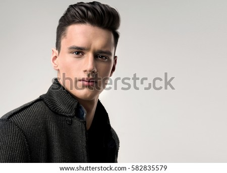 Fashion portrait of a handsome man with trendy hairstyle in a stylish jacket . #582835579