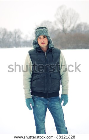 Fashion portrait of a handsome young man enjoying himself in winter