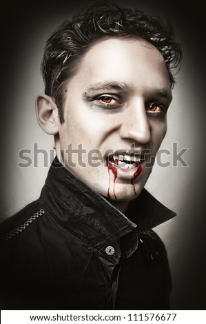 Fashion portrait of a handsome young man with vampire style bangs, blood and  make-up. studio shot.