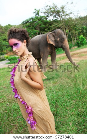 Fashion portrait of a model with an elephant in the background.