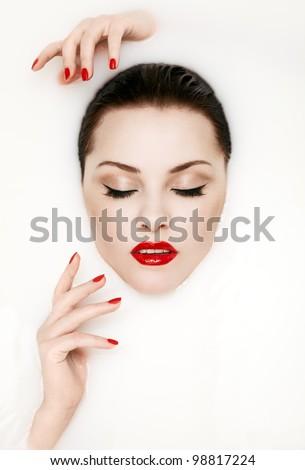 Fashion portrait of a sexy woman face in white milk - stock photo