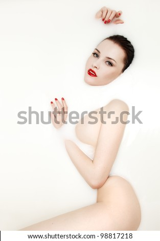 Fashion portrait of a sexy woman in white milk