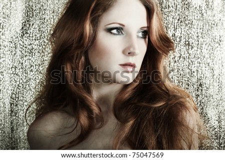 Stock Photo Fashion portrait of a young beautiful redheaded woman on a gold background