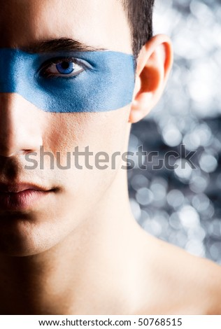 Fashion portrait of a young man with a blue make-up