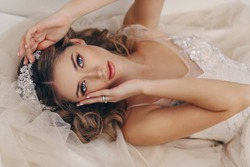 fashion portrait of beautiful bride with blond hair in luxurious wedding dress and accessories
