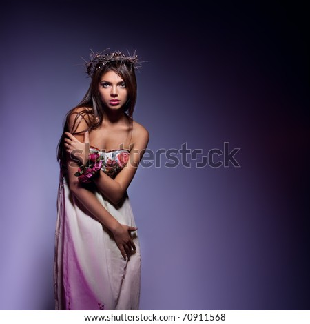 Fashion portrait of beautiful model wearing a long dress. Studio shot.