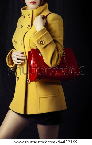 Fashion portrait of beautiful woman in yellow spring or autumn coat with red bag
