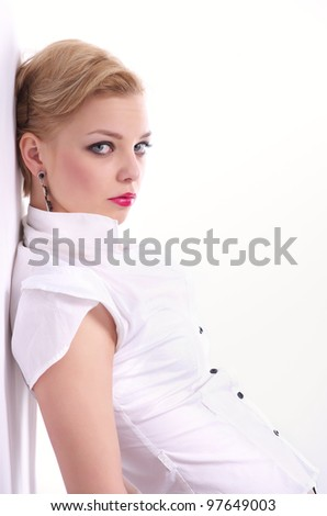 Fashion Portrait of beautiful woman leaning against the wall