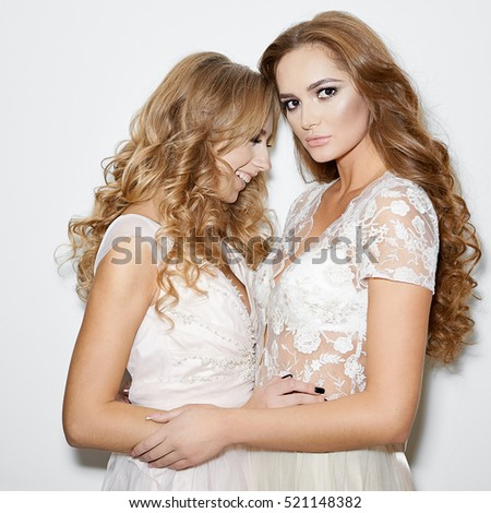 Fashion portrait of beautiful women models in white dresses on white background #521148382