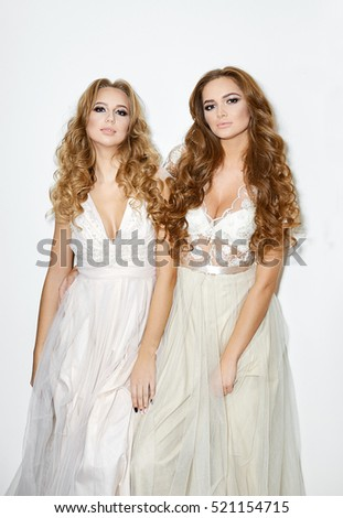 Fashion portrait of beautiful women models in white dresses on white background #521154715