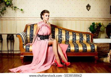 fashion portrait  of beautiful young female model lady with hairstyle in bright pink dress in interior sitting on the sofa