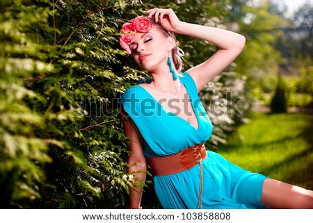 fashion portrait  of beautiful young female model lady woman with hairstyle in bright blue  dress posing outdoors lying in green grass near bush with flowers in hair