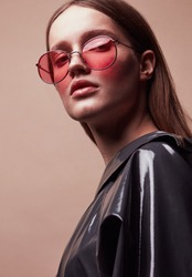 Fashion portrait of beautiful young woman in round red sunglasses and grey latex jacket posing in studio