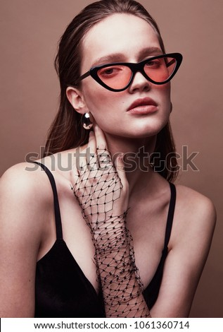 Fashion portrait of beautiful young woman in sunglasses with red lens, black dress, with massive earrings and veil on hand - Shutterstock ID 1061360714