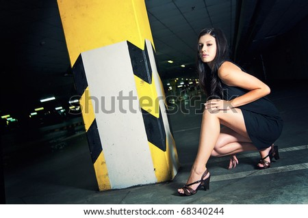 Fashion portrait of beautiful young woman posing in underground garage