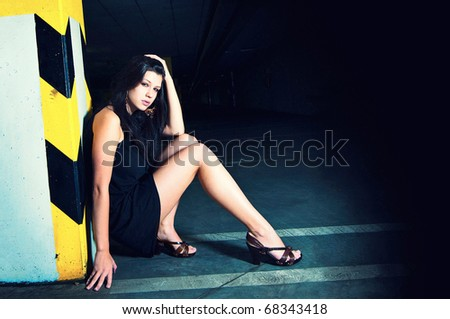 Fashion portrait of beautiful young woman posing in underground of shopping center