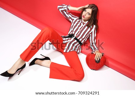 Fashion portrait of beautiful young woman. Red pants, red handbag, blouse, bright red background