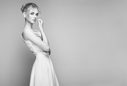 Fashion portrait of Beautiful Young Woman with Blond Hair. Girl in white Dress on White Background. Black and White photo