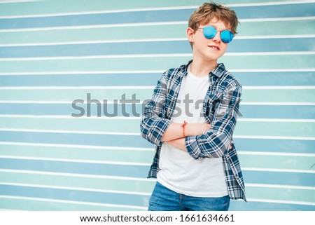 Fashion portrait of caucasian blonde hair 12 year old teenager boy dressed t-shirt and checkered shirt in blue sunglasses posing on turquoise blue background wall background. Teens fashion concept. Stock photo ©
