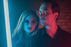Fashion portrait of couple: beautiful woman and handsome man posing in colorful bright neon uv blue and red lights. Models wearing trendy glasses. Club, disco style