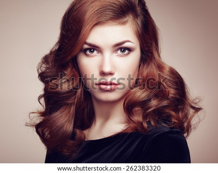 Fashion portrait of elegant woman with magnificent hair. Brunette girl. Perfect make-up. Girl in black dress. Curly hair