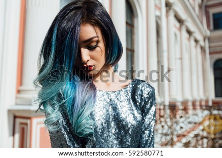 Fashion portrait of gorgeous girl with blue dyed curly hair long. The beautiful evening cocktail dress. Professional makeup and hair styling. Vintage old aristocratic building. Close-up